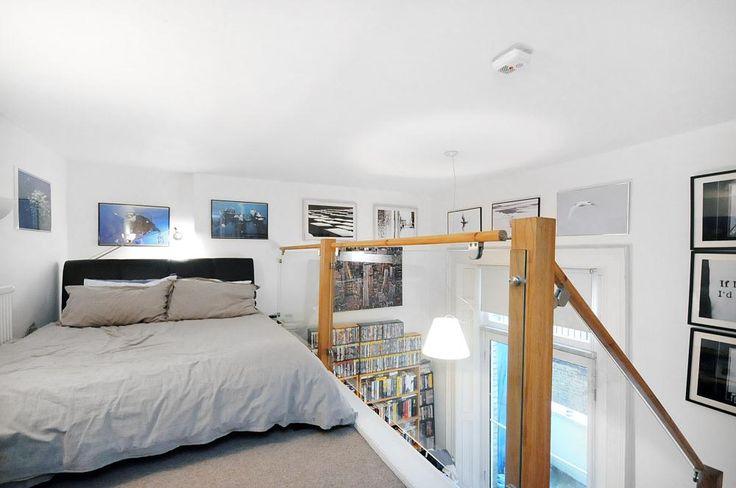 photo of white bedroom mezzanine with glass balustrade