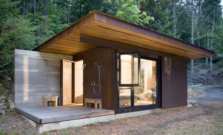 An outdoor shower sits just outside the sleeping area. The petite lodge requires virtually no maintenance, and is the perfect retreat for a true nature lover.   - HouseBeautiful.com