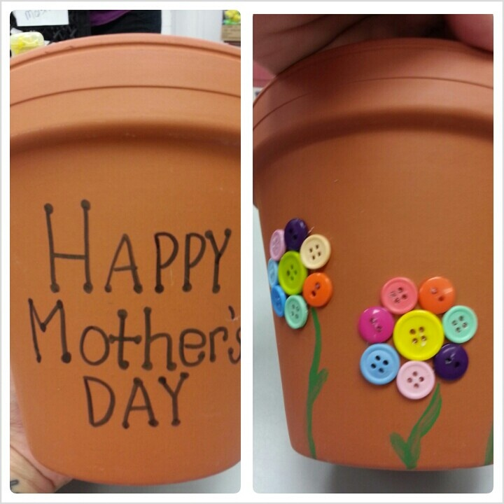 Hot glue buttons to a terra cotta pot for an easy craft