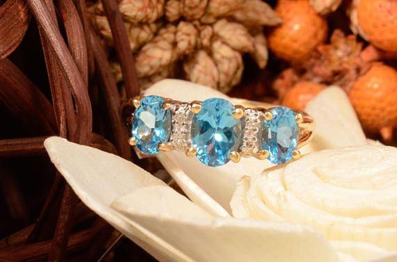 ¡Excelente estado! Este precioso anillo de topacio y diamante azul se encuentra en oro amarillo 14K macizo oval tres con topacios azules naturales de corte y se acentúa con cuatro diamantes. El centro azul topacio medidas 7 x 5 y el 6 por la medida 4 dos lado gemas. Pesa 3,8 gramos y es un tamaño 7.75.  Sobre nosotros  Somos una pequeña empresa de propiedad familiar, proporcionando más de 27 años de servicio en nuestra área local. Somos joyería de #1 de NH y han sido por voto cada año por…