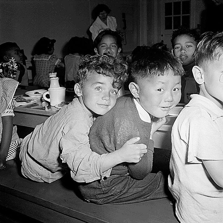 A Japanese-American boy gets a hug from his pal during lunchtime at a Public School in CA, April 1942. soon after, Japanese children and parents were evacuated during World War II to War Relocation Authority centers.