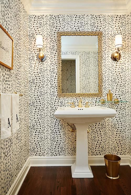 Chic powder room boasts walls clad in Thibaut Tanzania Wallpaper lined with a white pedestal sink ...