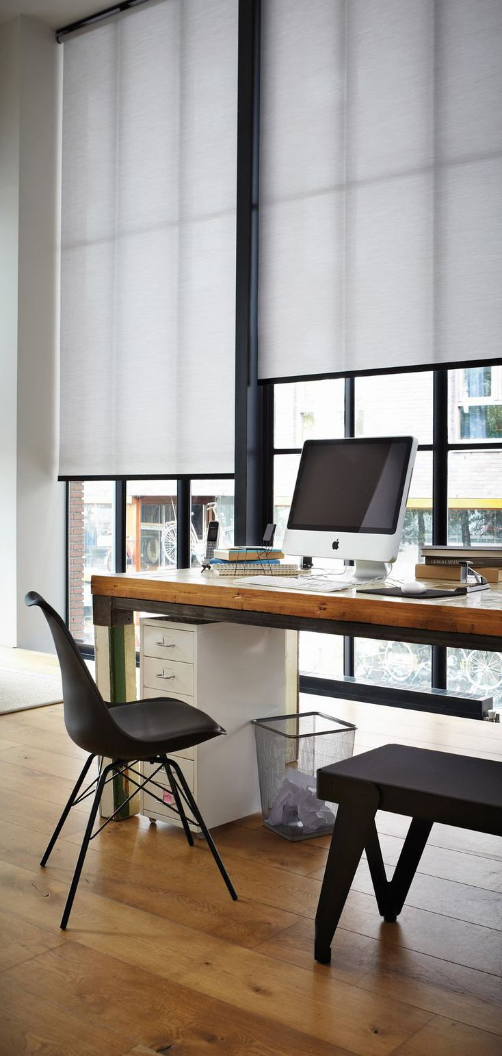 Create a working style in an urban home office with a striking black and white and roller shades.