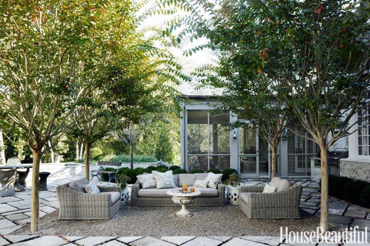 """Une cour de gravier sur la terrasse arrière définit le salon extérieur de la maison de Jeannette Whitson à Nashville.  Les myrtes de crape forment un «plafond» sur les meubles: un canapé et des chaises de Provence de Restoration Hardware, une ancienne urne de jardin transformée en une table basse et des tabourets de jardin en céramique.  """"C'est une telle zone abritée, les oiseaux aiment nicher dans les arbres"""", dit Whitson.  """"Parfois, on dirait que tu es dans une volière"""".  Les pavés de…"""
