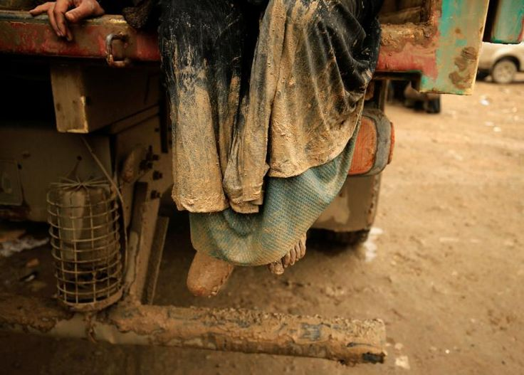 A displaced Iraqi woman who fled her home during a battle between Iraqi forces and Islamic State militants, arrives covered with mud at a checkpoint to be transfer to the Hammam al-Alil camp, in Mosul. REUTERS/Thaier Al-Sudani