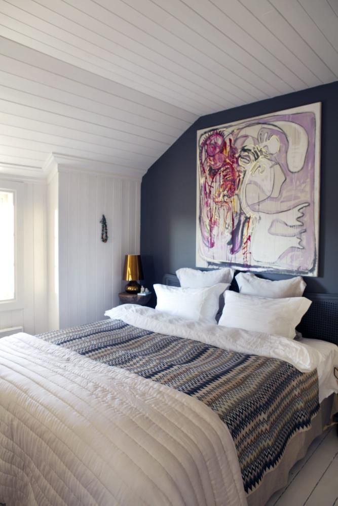HOVEDSOVEROM. Vegger og tak er eggehvite,mens det gamle tregulvet er lysegrått.Sengegavlen og veggen bak sengen ermalt stålgrå. Lyst sengeteppe i silke er fraAnouska, pleddet er fra Missoni. Lampener fra Kartell og bildet er malt av ThomasKnarvik, Galleri Semmingsen.