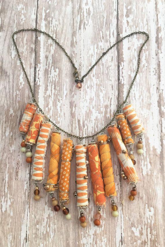 Este collar naranja declaración es verdaderamente uno de una clase. Cada grano era hecho a mano. Abalorios de tubo de tela hicieron envolviendo y rodando la tela, en diferentes tonos de naranja y blanco. La tela fue rodado, fue envuelto con el alambre y acentuado con los granos de oro, bronce y perlas. Cada grano de tubo de tela tiene un dangle de grano de alambre envuelto hecha de perlas de vidrio en tonos de naranja, marfil y tan. Los abalorios de tubo son alambre envuelto en una cadena de…