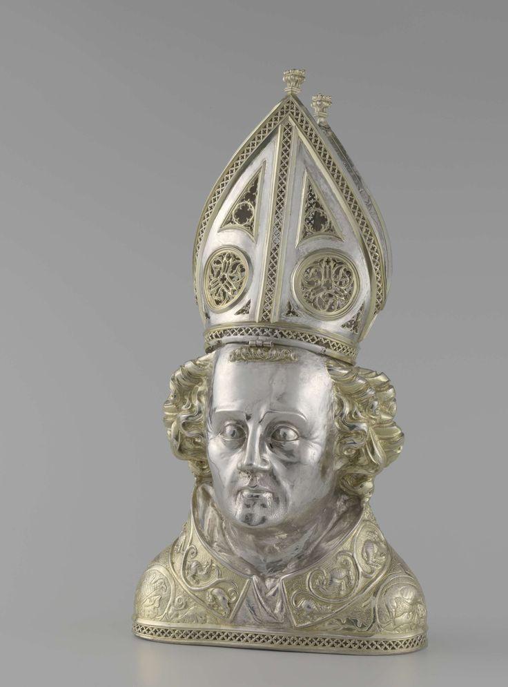 Elias Scerpswert | Bust of Saint Frederick, Elias Scerpswert, 1362 | Reliekhouder voor een deel van de schedel van de H. Fredericus, gedreven, gedeeltelijk verguld en staande op een rand van open traceerwerk. De schouders zijn bekleed met een kazuifel, waarop ingedreven rankenornament en vogels op een geponste grond. Daarboven draagt hij de amict, versierd met draken en ranken in reliëf. De wijduitstaande krullen, die het gehele hoofd omsluiten, zijn aan de zijkanten symmetrisch…