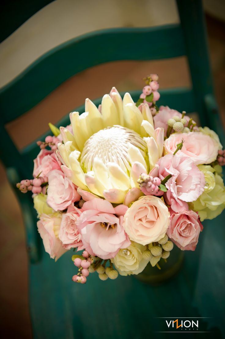 King protea bouquet with Esperanza roses, lisianthus, pink snow berries and cluster roses. Thanks to Vizion Photography