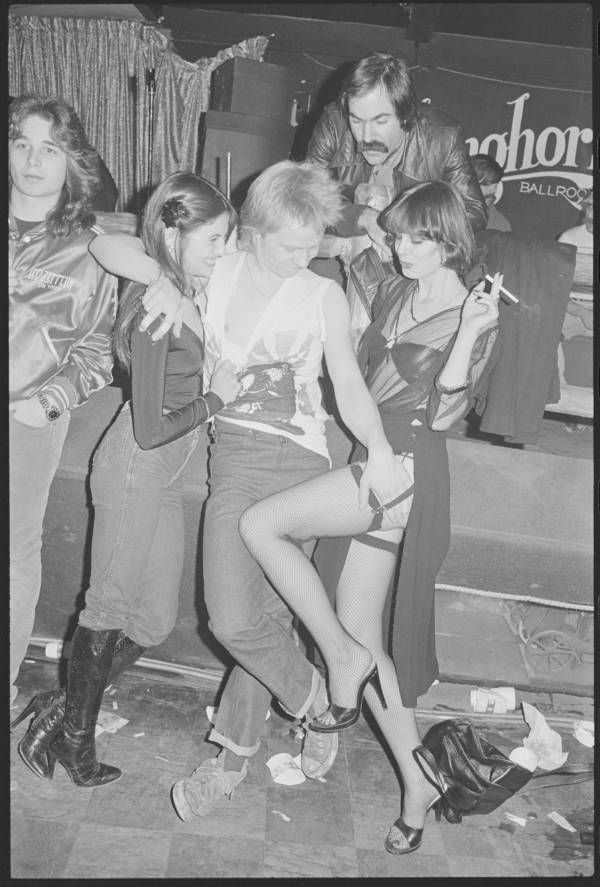 Sex Pistols guitarist Paul Cook with two women. Nancy Spungen wasn't the only groupie that followed the band around. Location unspecified. 1978. Lynn Goldsmith/Corbis/VCG via Getty Images