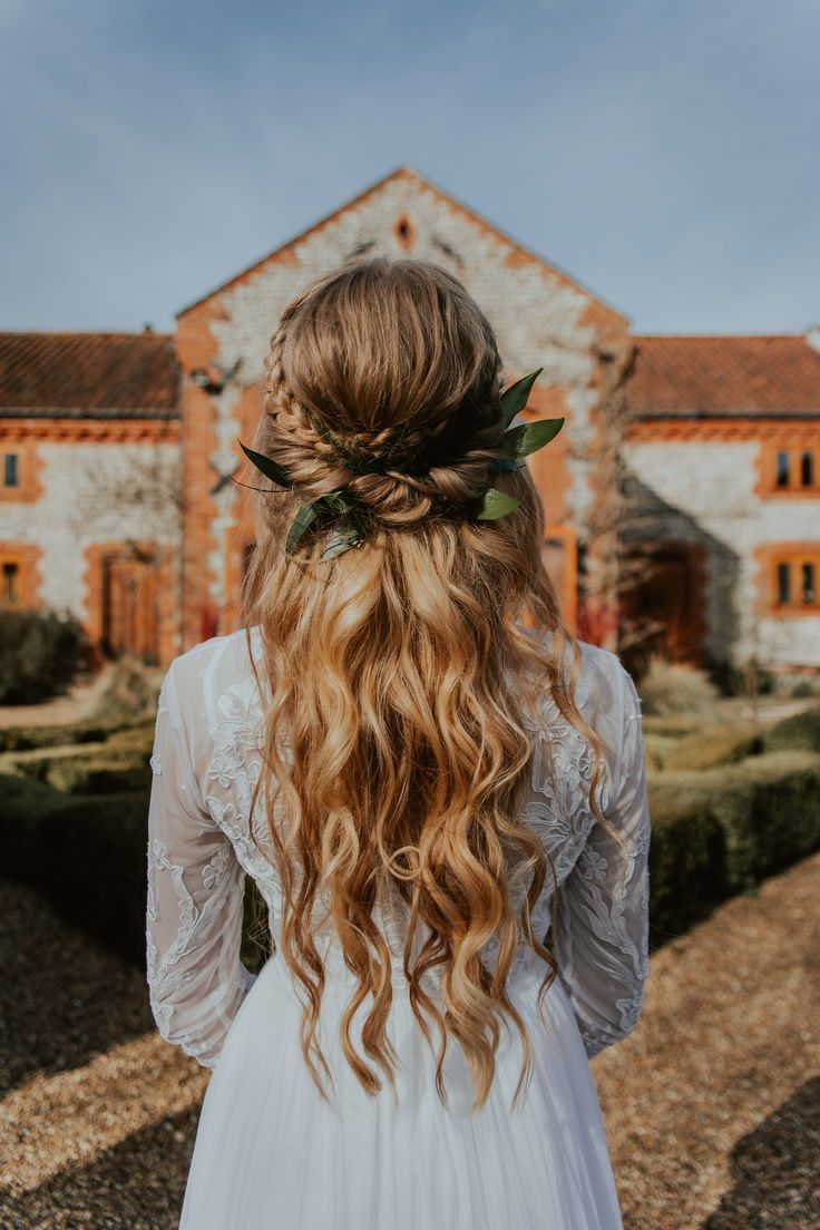 half up, half down wedding hair with a braid and greenery