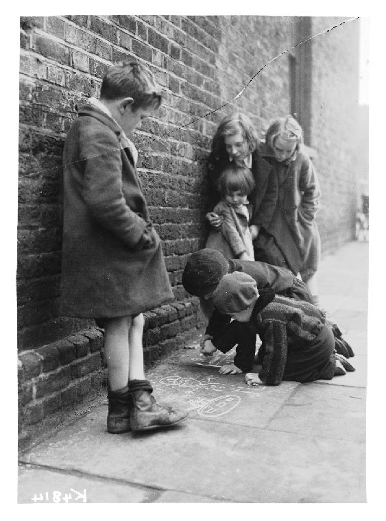 A group of children drawing with chalk on the pavement, taken in November 1941 by D H Calcraft of London