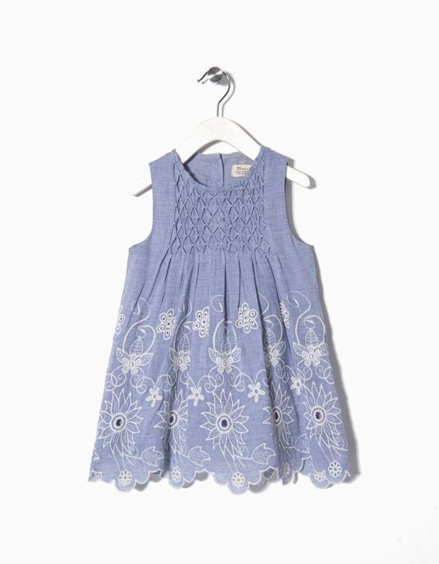 Vestido em cambraia 100% algodão com bordados e jogo de pregas à frente para bebé menina. Forro 100% algodão. Três botões atrás para vestir facilmente.