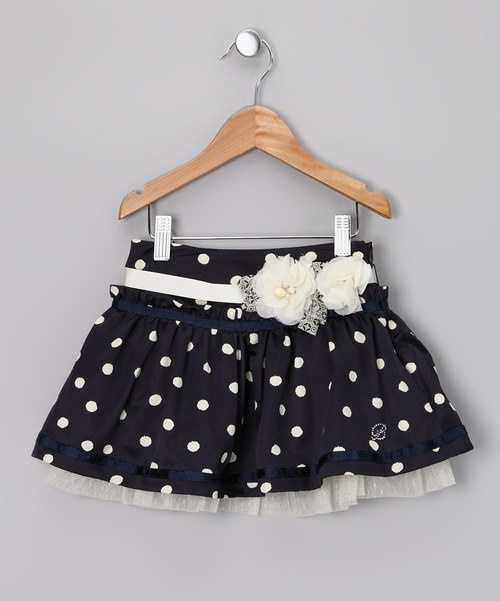This frilly and kicky skirt packs a lot of sweet and sassy personality into one small polka dotted package. Underneath its pretty pleats and ribbon detailing lie a fabulously full layer of tulle and a peekaboo layer of delicately dotted Swiss lace. The removable ribbon belt easily attaches with a handy hook and loop closure and boasts beautiful blooms with shimmering gem centers to perfectly finish off one stylish skirt while the sleek waistband hides an interior...