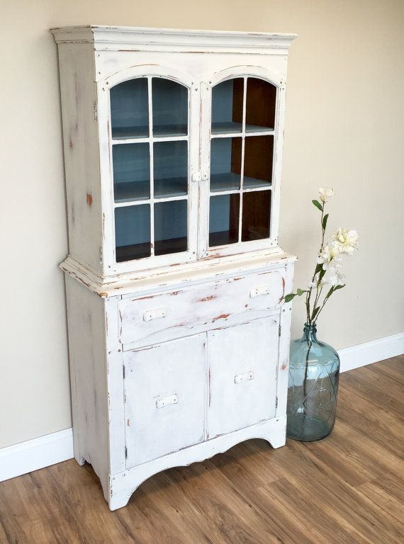 This small white country style hutch has been painted in a very rustic farmhouse style. It has two glass doors that open to reveal two shelves