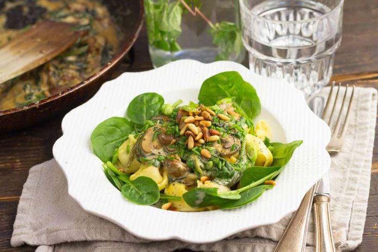 Recept voor tortellini voor 4 personen. Met zout, water, olijfolie, peper, roomkaas, bosui, champignon, spinazie, tortellini (pasta), knoflook, ui en pijnboompitten