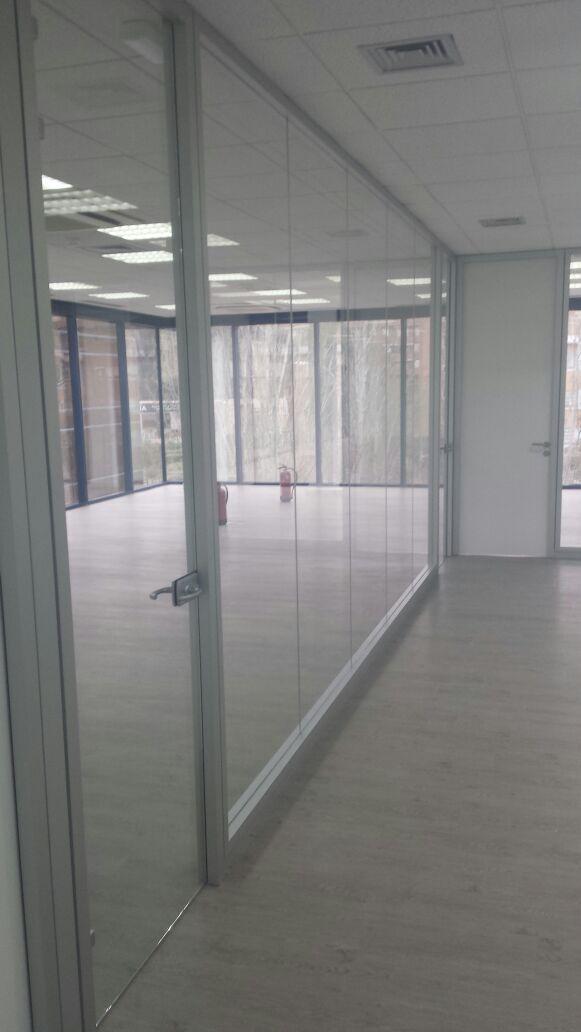 Frente sala juntas acristalado con modelo Lyon. Puerta acristalada de vidrio templado suelo a techo con cerradura y manivela. Montado sobre perfiles de aluminio anodizados en color plata.