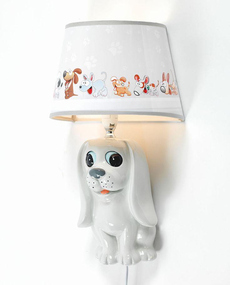 Ea Belysning står bak denne kjempesøte vegglampen i malt gips. Lampen har form som en søt hund i lyse farger og en skjerm i grått og hvitt med bilder av morsomme hunder som løper.