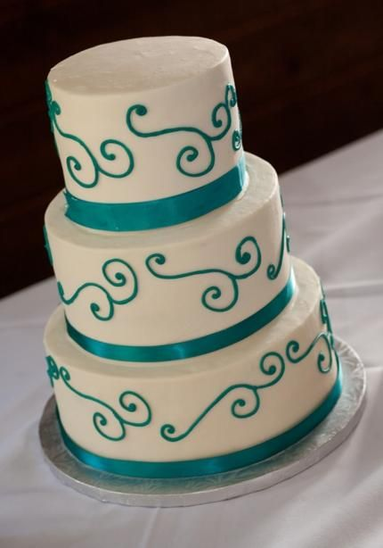 Turquoise wedding cake. Maybe w/purple and with lace. simple but elegant, I think this is somewhat of a style we are going for, we'd make a few changes.