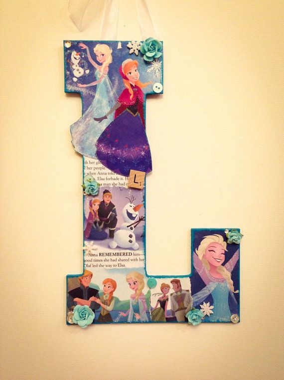 Any wooden letter decorated in Disneys new movie Frozen featuring:  **Elsa and Anna**   This wooden letter is all about the Disney princesses Elsa and Anna. The letter is decorated with scenes from the new movie Frozen and text from the storybook. Images of Elsa, Anna, Olaf, and other characters adorn the letter. Vintage buttons and jewel snowflake accents add a touch of whimsy. Glitter accents make Elsas powers come to life and Annas spirit sparkle.  Back of letter is painted shimmery…