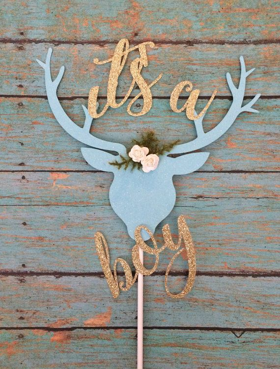 Complete your boho chic baby shower decorations with the ultimate cake topper! It can also be used to decorate your flower arrangements!  This listing is for: 1 light blue lightly glittered card stock deer head with antlers adorned with 2 or 3 white flowers and greenery.  This cake topper reads Its a Boy in gold glitter. It measures roughly 7 wide and 5.89 tall - it is the perfect topper to help celebrate your little brave. It can be customized to any other color combination at no…