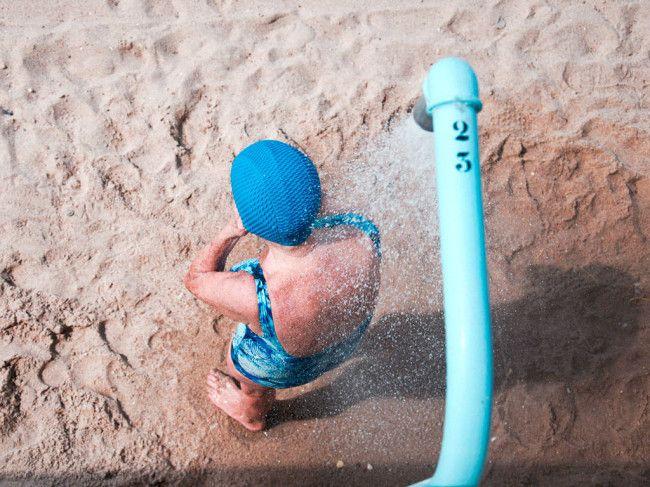Eine Frau in blauem Badeanzug und mit blauer Badekappe unter einer Dusche am Strand.
