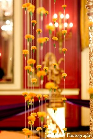 The custom mandap is draped with yellow floral garland for the Hindu wedding ceremony.