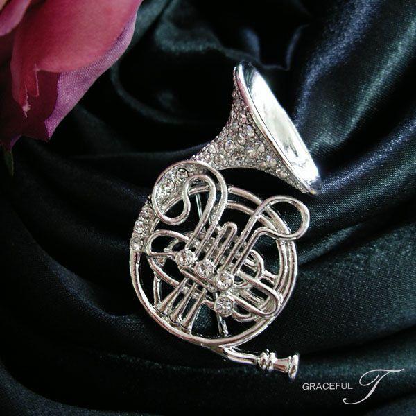 上品でエレガントなスワロフスキーストーンが煌めいて。 マウスピースからベルまでリアルなデザイン性が印象的な 楽器モチーフのブローチ ホルンです。
