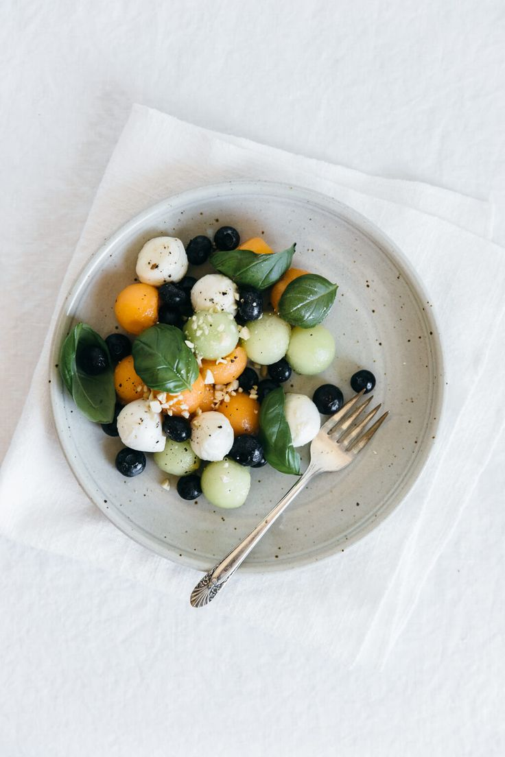 Melon Mozzarella Salad with Basil 1 cantaloupe melon 1 honeydew melon 2 cups blueberries 1½ cups mozzarella balls 1 cup fresh basil leaves, loosely packed 1½ tbsp olive oil ½ tsp white balsamic vinegar ½ tsp honey salt and pepper, to taste chopped raw cashews, for garnish