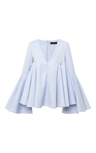 Quickly moving up the fashion ranks for its inspired womenswear, **ELLERY** fuses elegance with a gamine spirit and hints of the avant-garde. A sartorial masterpiece, this cascading blue top features a flared bodice and romantic exaggerated bell sleeves.