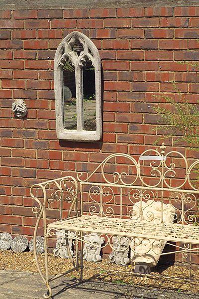 K cihlové zdi se hodí romantický zahradní kovaný nábytek. Zrcadlo promítá obrázky z okolí a prostor opticky prohlubuje.
