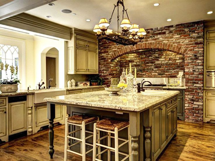 Mediterranean style kitchen with brick wall above oven and granite island