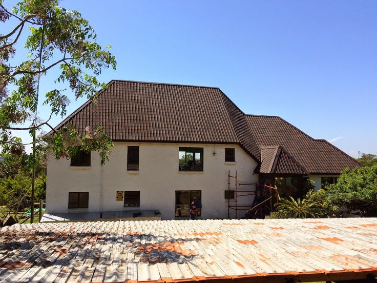 A big old thatched house converted to shaded brown Onduvilla tiles - the angles of the roof tiles look stunning