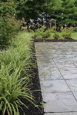 Stone patio, black mulch, grasses, lush, modern country home Completed by Leaf Garden Design Inc.  | oakdale Rd
