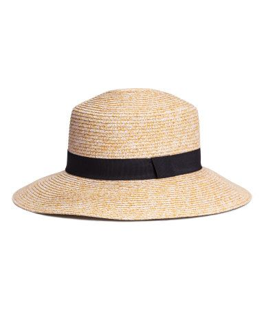 Wide-brimmed hat in braided paper straw with a grosgrain band. Width of brim 3 1/4 in.