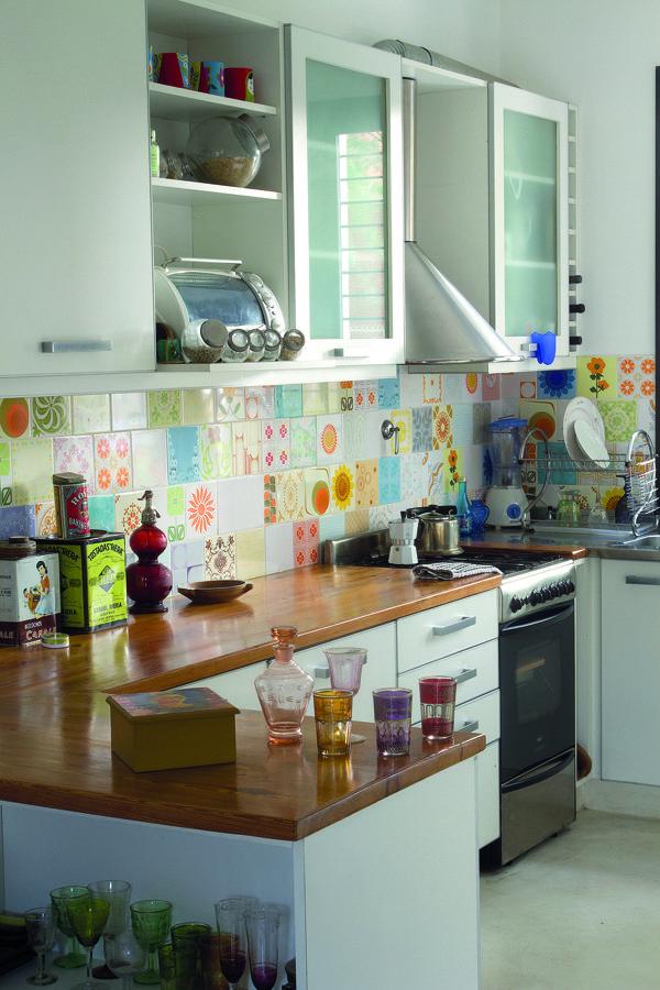 ARTE VARIOPINTO (CUTE) -La cocina, con diseño en U, conserva el amoblamiento de obra. La mesada se resolvió en todo su perímetro y es de lapacho laqueado.  Es el mix de azulejos de reposición, todos diferentes, que cubre la pared entre la mesada y las alacenas el mayor foco de atracc…