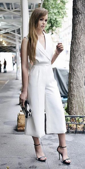Kristina Bazan of Kayture heading to the W magazine lunch event in a tailored white V-neck wide-legged jumpsuit by Cameo the Label.