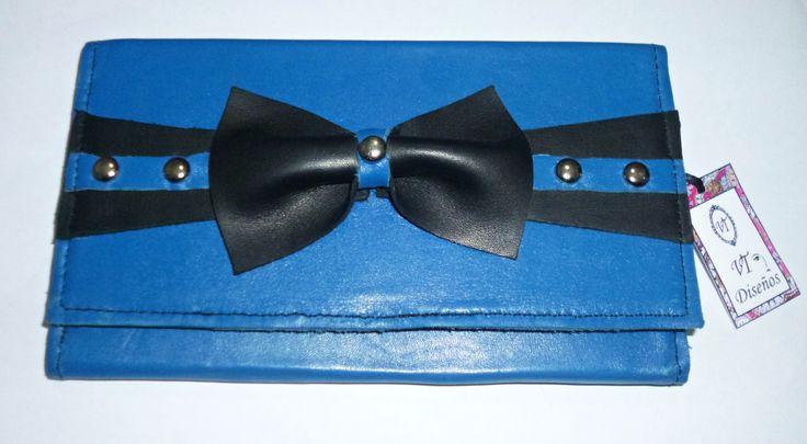 Billetera de cuero, color azul eléctrico, con detalle de moño en cuero color negro, con tachas plateadas.