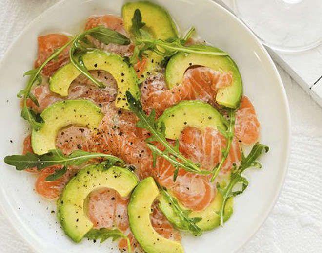Carpaccio de salmón y aguacate  Con cuidado cortar el aguacate para que quede muy fino.  Añadir el salmón ahumado ya fatiado.  Añadir rucula o brotes, aceite de oliva y limón con pimienta.