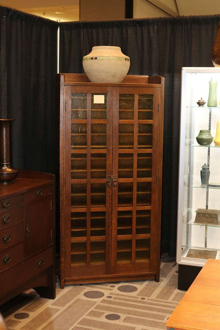 California Historical Design at Craftsman Weekend 2016 | Gustav Stickley two-door custom made wine cabinet.  Holds approximately 150-160 wine bottles.  Signed with early Eastwood label.  Original finish.  Original amber glass.  73″h x 36″w x 16″d; Hillside Pottery cement jardiniere with inset square tiles.  Unsigned.  Perfect condition. 12″h x 16″d