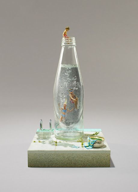 Diorama in water bottle. I'd say a clear resin was used with the bubbles left in.