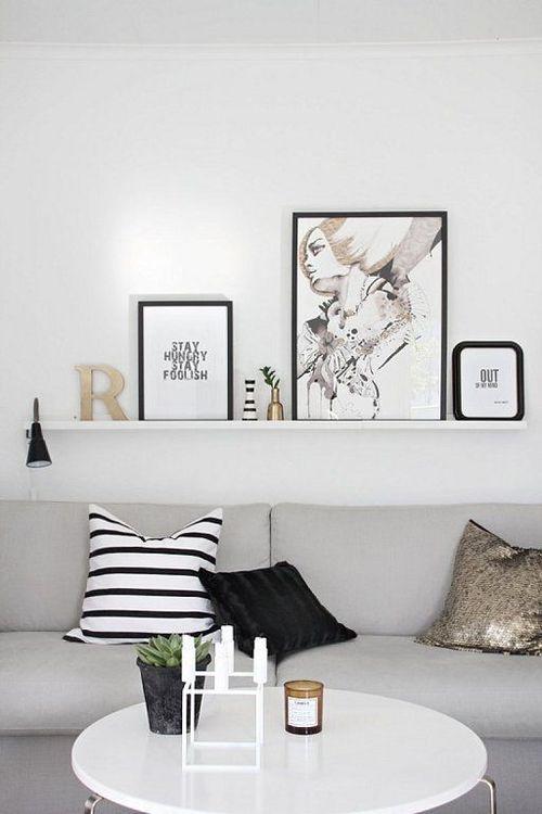 Prateleira única acima do sofá com pequenos posters apoiados mesclados com pequenos objetos decorativos