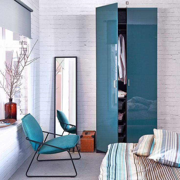 A bedroom with a black-brown wardrobe with turquoise high-gloss doors, black-brown mirror and an easy chair with turquoise cover