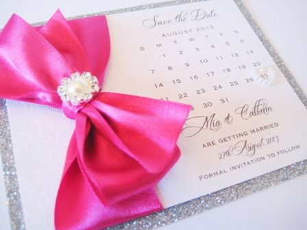 Wedding calendar save the date cards designed with sparkly silver glitter border and cerise hot pink ribbon bow. Styled with a pretty pearl brooch. The cards are personalised with the wedding day details and have a little heart pearl on the wedding date.