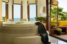 Luxury Rounded Bathtub With Unique Carving Overlooking Sea View Through Glazed Window In Deluxe Bathroom Interior