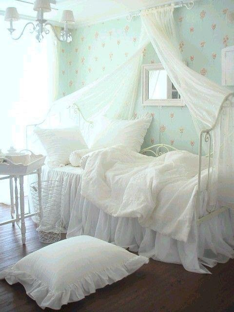 dreamy white bedding and canopy with a soft aqua wall