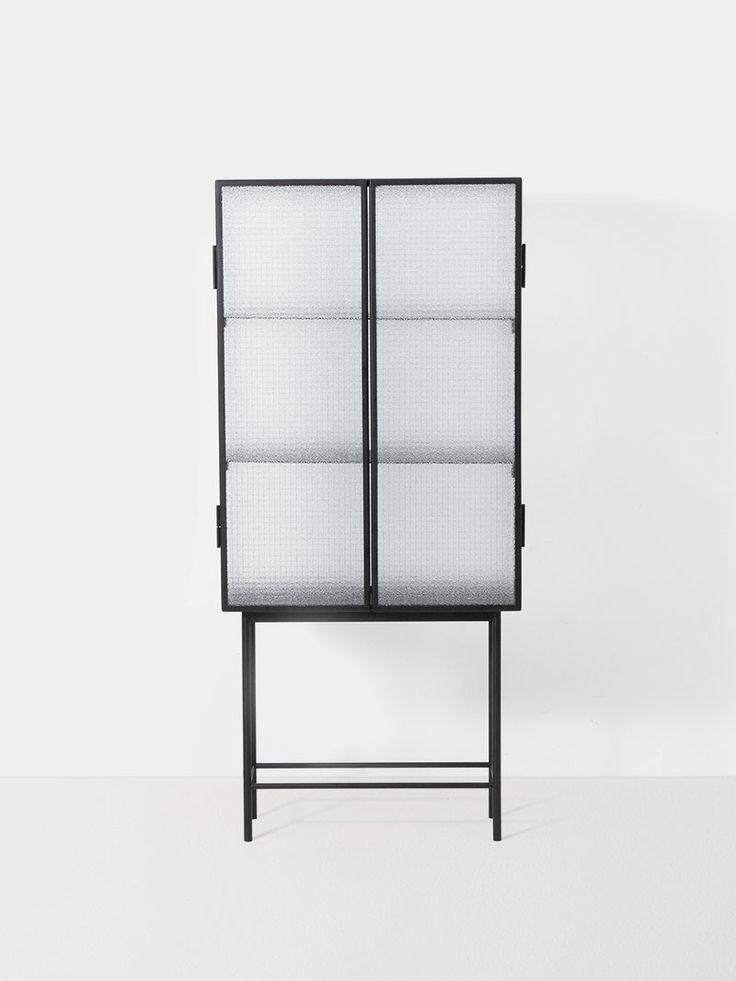 Bei dieser freistehenden Vitrine aus elegantem pulverbeschichtetem Metall und Drahtglas ziehen sich die Gegensätze an.