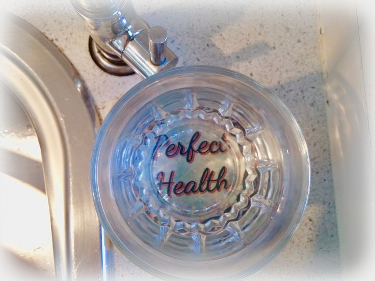 """A glass of filtered water rests on a stone marble coaster with the words: """"Perfect Health"""". Dr. Masaru Emoto discovered that the water will absorb the vibration of the words!"""