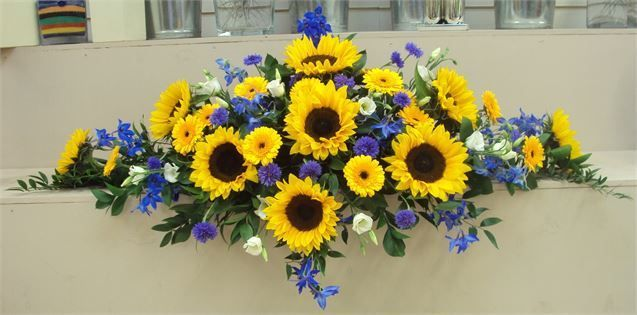 Sunflowers delphiniums long & low top table arrangement from The Flower Shop - The Flower Shop
