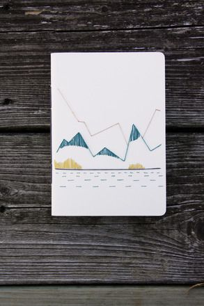 Avec son format A6, on l'emporte partout avec nous, c'est pratique! Un paysage de montagne au bord d'un lac brodé sur papier canson couleur blanc cassé. L'intérieur est en p - 19367401